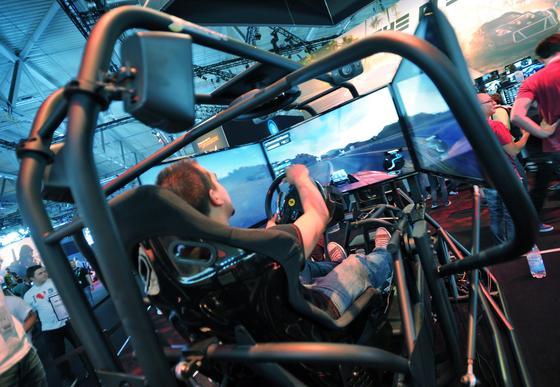 Ein Besucher spielt in einem Rennsimulator The Crew, ein Autorennspiel von Ubisoft für PS4 und XBox One.