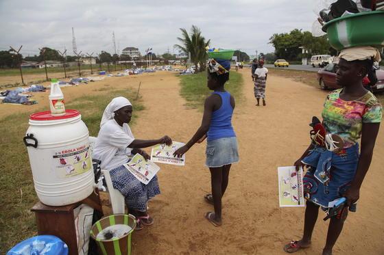 In Liberia verteilt eine Frau Broschüren, um die Bevölkerung über Ebola aufzuklären. Laut Weltgesundheitsorganisation WHO starben in Westafrika an dem Virus bereits über 1000 Menschen. Die Länder suchen händeringend Medikamente.