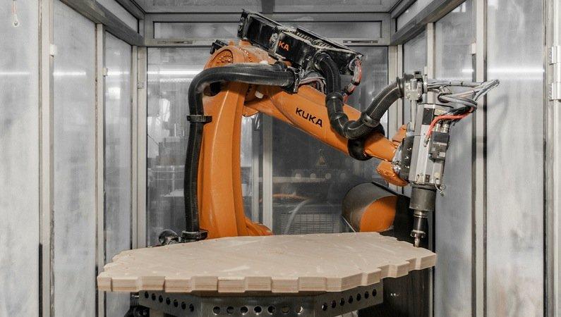Ein Roboter bringt die Holzplatten in Form – mit einer siebenachsigen Fräsmaschine auf Basis der digitalen Konstruktionszeichnung. Die Maßtoleranz der Bauteile betrug gerade einmal 0,86 Millimeter.