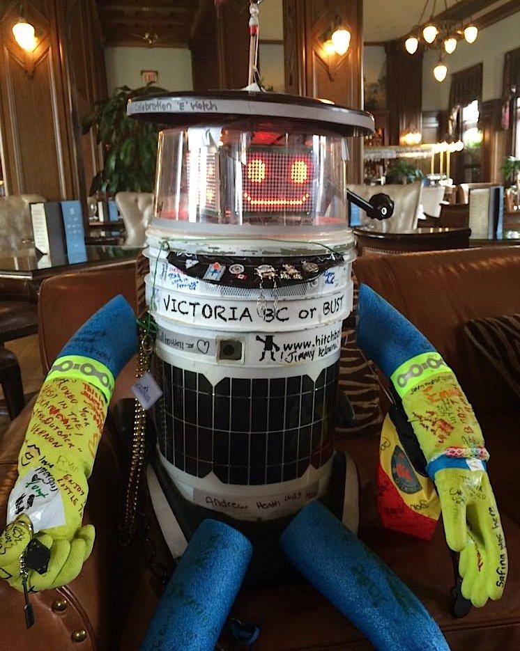 Geschafft: Offenbar ermattet sitzt hitchBOT in einem Lokal auf Vancouver Island. Deutlich zu sehen sind die Autogramme auf seinen Armen und Beinen.