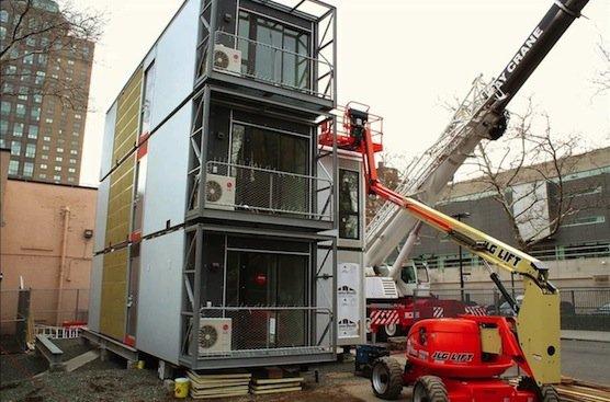Kräne stapeln die Container aufeinander: Auf dem Dach ist eine Solaranlage für die Stromversorgung installiert.
