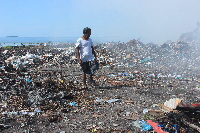 Der Gastarbeiter Khaled aus Bangladesch läuft durch schwelende Abfallreste am 21. März 2014 auf der Müllinsel Tilafushi, Malediven. Die Malediven-Insel war einst eine türkisblaue Lagune im Indischen Ozean, bis die Regierung in den 90er Jahren beschloss, dort einen Großteil des Mülls des Landes abzuladen.