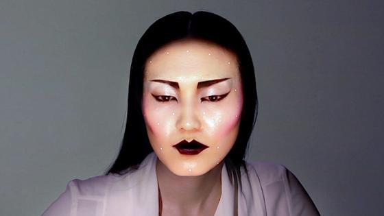 Das Gesicht dieses Modells ist in Wirklichkeit ungeschminkt. Das Make-up des Künstlers Nobumichi Asai ist projiziert und folgt den Bewegungen des Gesichts.
