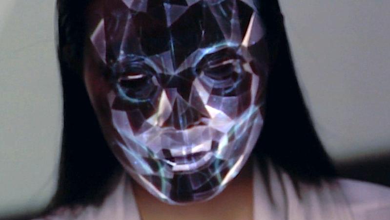 Hier wird es gruselig: Nobumichi projiziert abstrakte Formen auf das Gesicht des Modells und lässt es wie einen Roboter erscheinen.