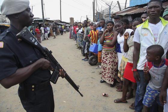 Soldat im Slum von Monrovia in Liberia: Inzwischen ist Ebola in fünf afrikanischen Ländern ausgebrochen und hat 1600 Todesopfer gefordert. Forscher arbeiten Tag und Nacht an Medikamenten, die die Seuche bekämpfen können.