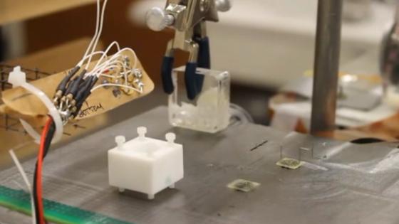 Die Mikroroboter auf diesem Bild sind die beiden hauchdünnen Scheiben in der rechten Bildhälfte. Der obere transportiert ein winziges Bauteil, ein schwarzes Plastikröhrchen.