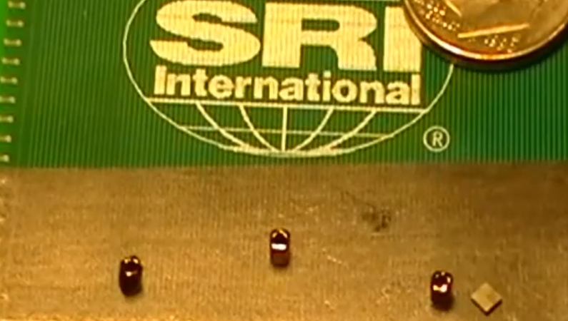 Dieser viereckige Mikroroboter in der rechten unteren Bildhälfte ist nur zwei Millimeter groß. Er kann die drei Hindernisse mit einer Geschwindigkeit von 35 Zentimetern pro Sekunde umkreisen.