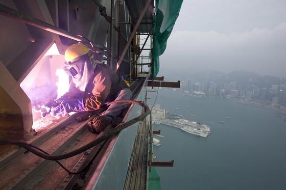 Ein Arbeiter bei Schweißarbeiten am International Commerce Centre (ICC), dem höchsten Haus Hong Kongs. Solche Verrenkungen führen im Laufe der Jahr oft zu Rückenproblemen.