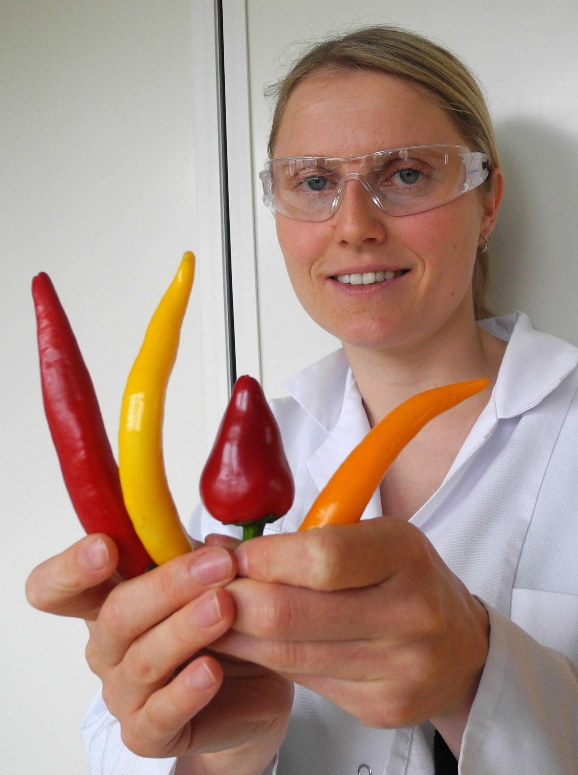 Désirée Schneider mit verschiedenen Chilischoten in den Händen: Die Ernährungswissenschaftlerinist der Frage nachgegangen, wie der Schärfereiz von Chili am besten neutralisiert werden kann.