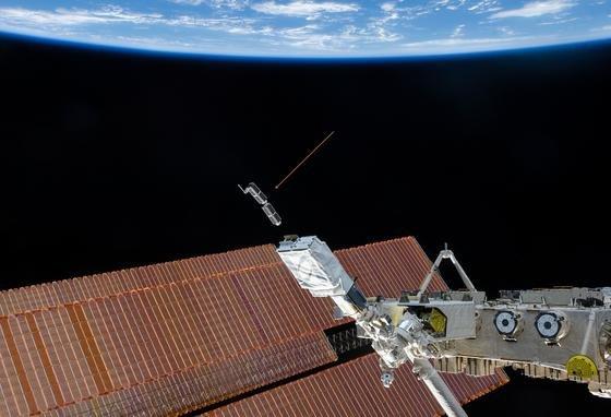 """Die Internationale Raumstation ISS setzt derzeit die Minisatelliten von Planet Labs aus (Pfeil). Diese enthalten Kameras, die laufend Bilder der Erde über das Internet anbieten sollen. Jetzt sind zwei Satelliten """"aus Versehen"""" ausgesetzt worden und kreisen auf einer falschen Umlaufbahn."""