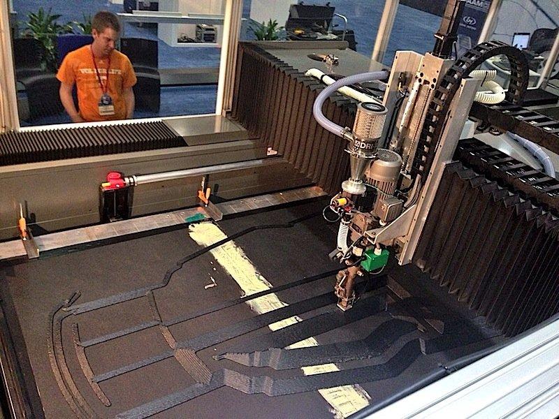 Der 3D-Drucker ist so groß wie ein Zimmer. Er braucht 44 Stunden, um alle Autoteile auszudrucken. Als Tinte benutzt er ein mit Kohlenstoff verstärktes Polymer namens Acrylnitril-Butadien-Styrol (ABS).