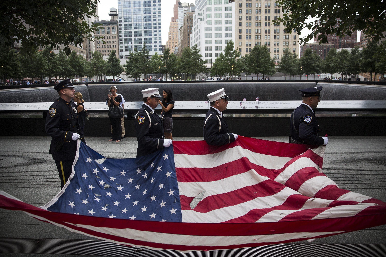 Gedenken an die Opfer des Terroranschlages vom 11. September 2001 in New York: Mitglieder der New Yorker Polizei und der Feuerwehr tragen am heutigen 11. September 2014 eine US-Fahne zu Ground Zero, um den mehr als 3000 Todesopfern des Anschlages zu gedenken.