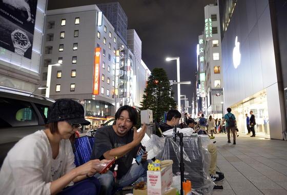 Apple-Fans sitzen in Tokio auf Klappstühlen in der Nähe eines Apple-Geschäfts. Auch sie warten auf den Verkaufsstart des iPhone 6 am 19. September.
