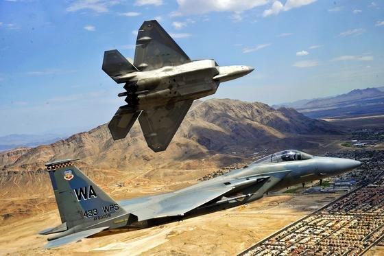 Das Überschall-Flugzeug F-22 Raptor (oben) flog nach syrischen Medienberichten 50 Einsätze gegen Stellungen der Terrorgruppe IS in Syrien. Es war der erste Kampfeinsatz des Überschall-Jets überhaupt. Im Bild ein Testflug in der Nähe derNellis Air Force Base in Nevada.Die Triebwerke liegen tief im Inneren der Maschine, damit das Radarecho minimal ist. Unten im Bild zu sehen ist eineF-15 Eagle.