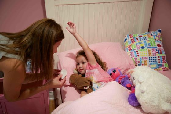 Eine Mutter klebt ihrem kranken Kind das Sensorpflaster unter die Achsel. Es misst die Temperatur die ganze Nacht. Im Notfall schlägt das Smartphone Alarm.