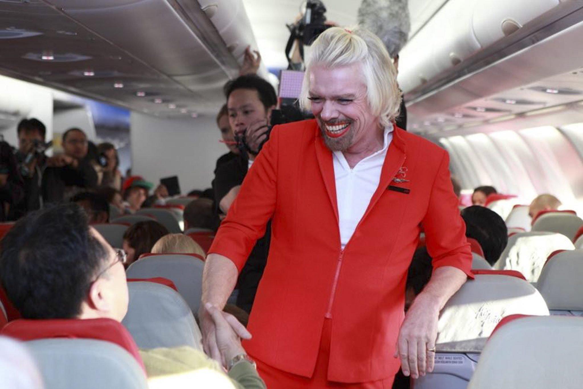 Branson, hier verkleidert als Sterwardess, weiß die Aufmerksamkeit der Medien auf sich zu ziehen. Kritiker befürchten, dass sein Urlaubsmodell Angestellte auch überfordern könnte.