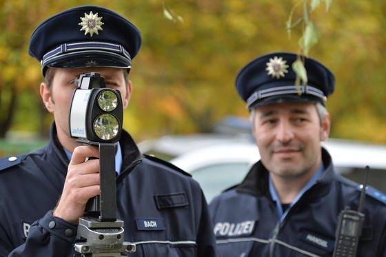 Polizeibeamte messen beim Blitzmarathon mit einem Lasermessgerät die Geschwindigkeit eines vorbeifahrenden Autos. Sollte die Radarpistole aus den USA nach Deutschland kommen, könnten sie zukünftig auch Simser am Steuer erkennen.