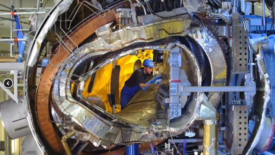 Ende 2011 war das Innenleben von Wendelstein 7-X noch sichtbar. Jetzt ist die ringförmige Anlage geschlossen. Vom Zentrum nach außen: das Plasmagefäß, eine der verwundenen Stellaratorspulen (silberfarben), eine ebene Spule (kupferfarben), die Stützstruktur (rechts) und das Außengefäß zusammen mit zahlreichen Kühlleitungen und Stromverteilern.