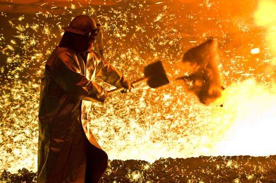 Ein Arbeiter in Schutzkleidung vor einem angestochenen Hochofen. Mit dem neuen Spektrometer soll sich die spätere Stahlqualität noch genauer prüfen lassen.