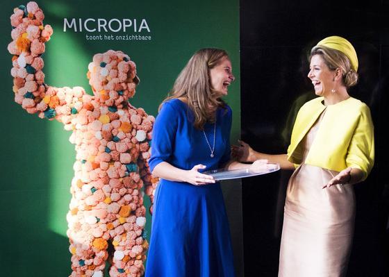 """Die niederländische Königin Máxima (r.) hat den weltweit ersten Zoo für Mikroben in Amsterdam eröffnet. Entsprechend ungewöhnlich war auch die Einweihung:Micropia-Direktorin Eveline Hensel überreichte der Königin eine riesige, gläserne Petrischale, auf die sie beide Hände drückte. Und so hinterließ Königin Máxima dem Zoo gleich unzählige """"königliche"""" Mikroben."""
