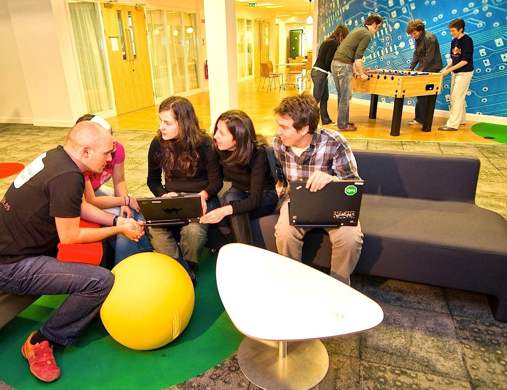 Bei Google liegen Arbeiten und Entspannen eng beieinander. Während einige Mitarbeiter vorne im Café arbeiten, entspannen sich andere beim Kickern.