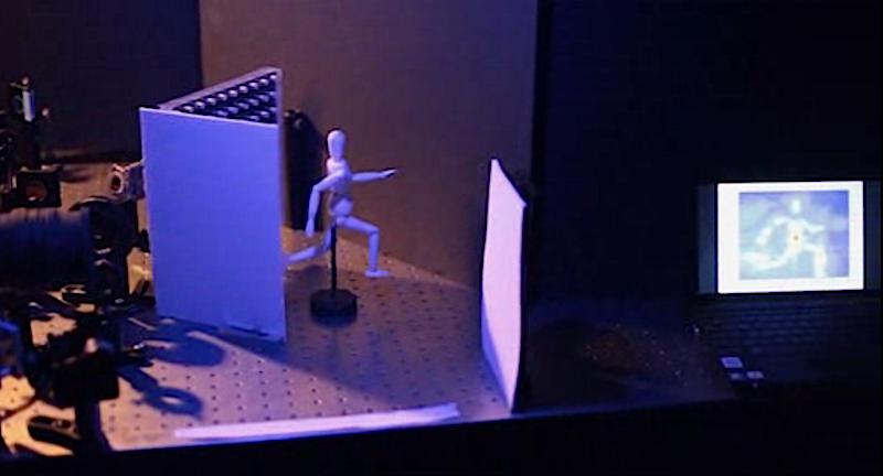 Versuchsaufbau des Kamerasystems: Die Kamera links im Bild schießt Photonen auf die weiße Fläche. Die Photonen werden zur Figur gelenkt, von dieser zurück zur Fläche reflektiert und treffen anschließend auf den Kamerasensor. Aus der Flugzeit einzelner Photonen lässt sich die Figur rekonstruieren (rechts auf dem Monitor).
