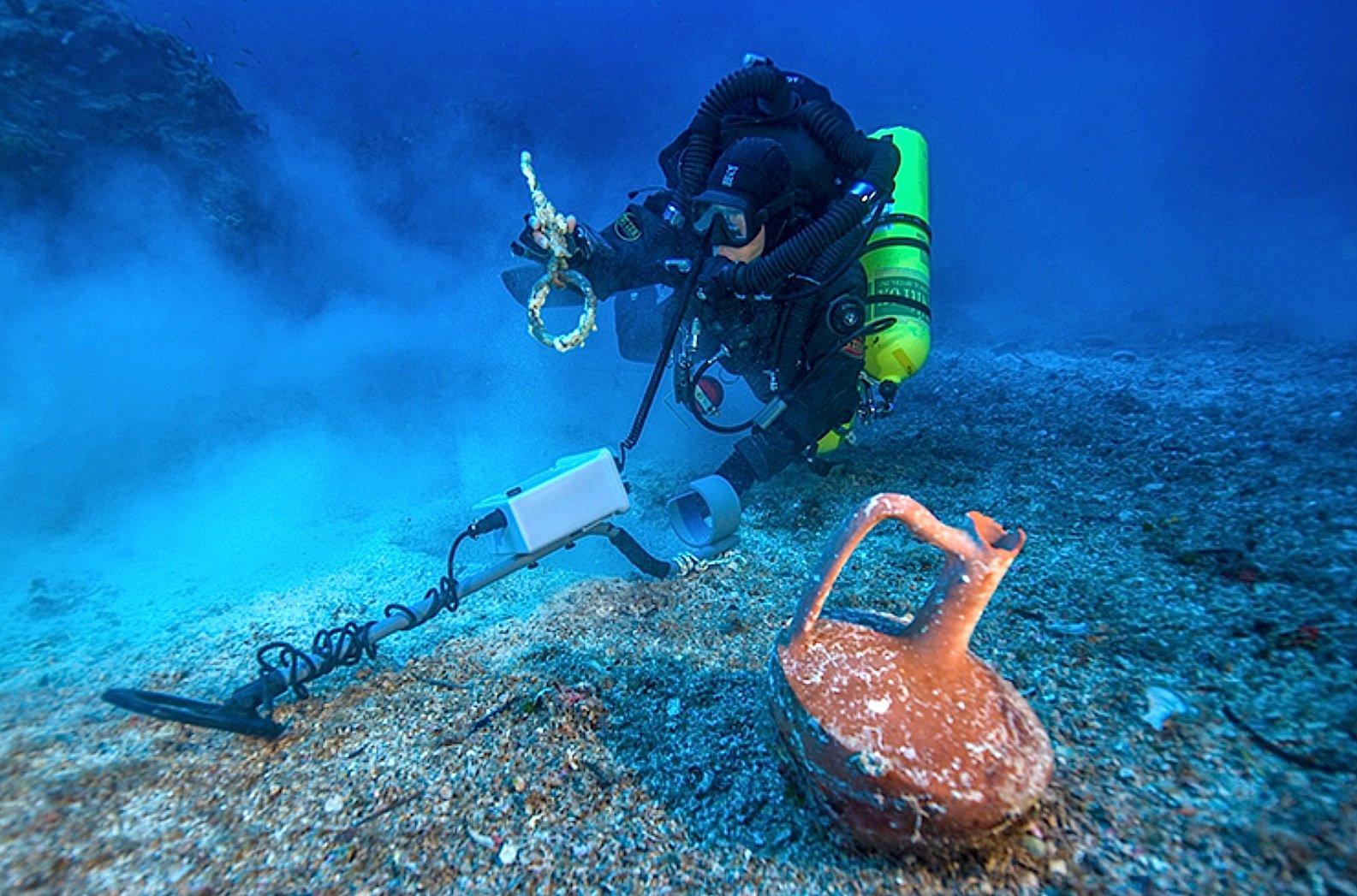 Mit Rebreather-Technologie gelangten die Taucher zumantiken Wrack vor der griechischen Insel Antikythera. Im Vordergrund zu sehen sind ein Keramikkrug und ein Bronzering der Takelage.
