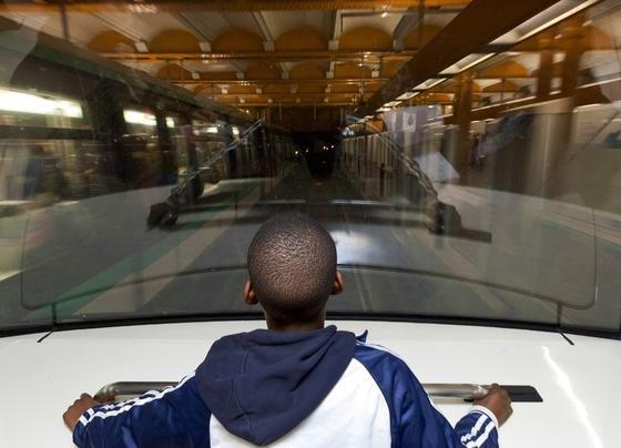 Ein Junge in einer fahrerlosen Metro genau dort, wo sonst der Fahrer sitzt: Die Pariser Metro betreibt zwei Linien mit fahrerlosen Zügen. In der Spitze ermöglicht die Technik einen 85-Sekunden-Takt, der mit gewöhnlichen Zügen nicht zu schaffen ist.