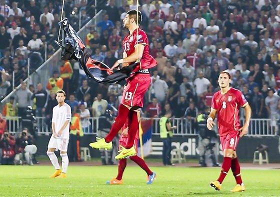 Der serbische Spieler Stefan Mitrovic, Innenverteidiger beim deutschen Bundesligisten SC Freiburg, bekommt die albanische Fahne zu fassen und reißt sie zu Boden.