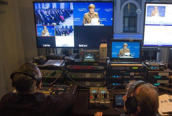 Techniker vor dem TV-Bild von Bundeskanzlerin Angela Merkel auf dem IT-Gipfel in der Handelskammer Hamburg: Merkel hat die Unternehmen aufgefordert, beim Netzausbau mehr Risiken einzugehen.