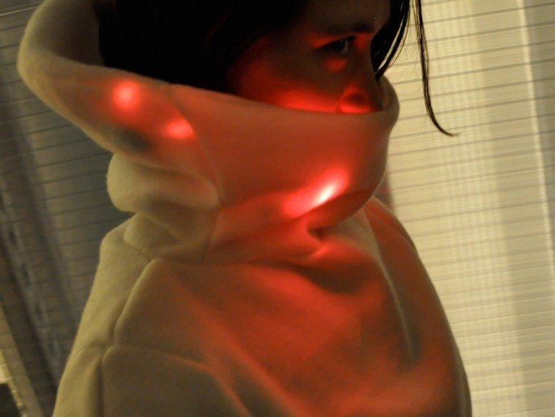 Die junge Frau ist entweder verliebt oder nervös. In beiden Fällen leuchtet der Kragen des Mood Sweaters rot.