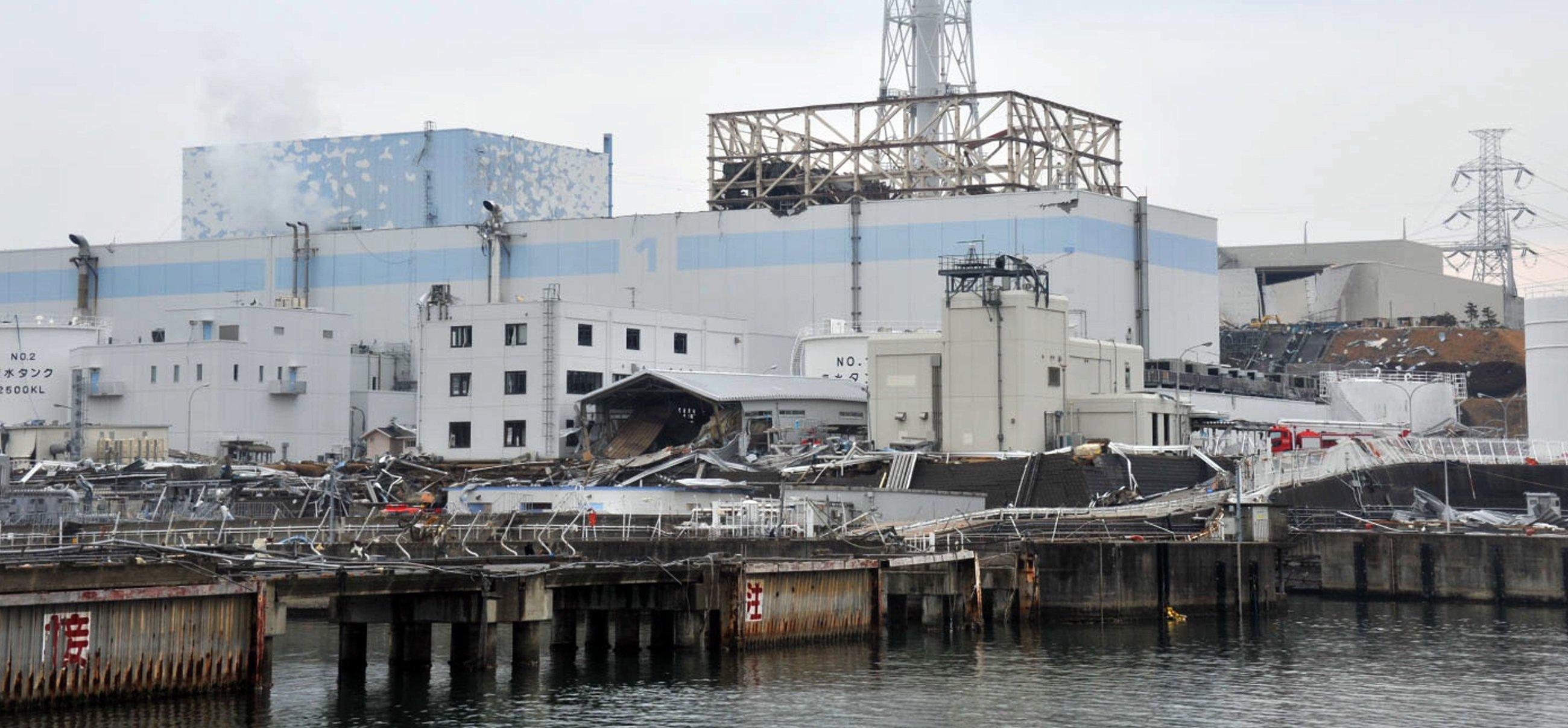 Ruine des havarierten Atomkraftwerks Fukushima mit den Reaktoren 1 (M) und 2 von der Seeseite aus:Ungelöst ist das Problem des steten Zuflusses großer Mengen Grundwasser in das Kraftwerk. Es vermischt sich teilweise mit dem Kühlwasser der Reaktoren und droht ins Meer zurückzulaufen.