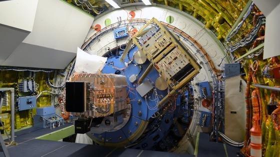 """An die blaue Tragestruktur des Teleskops ist derrechteckige, silbern glänzende Aluminium-Kryostat des FIFI-LS-Instruments montiert. Der Kryostat ist mit flüssigem Stickstoff und flüssigem Helium gefüllt, um die optischen Elemente und Detektoren auf die notwendigen tiefen Temperaturen zu kühlen. Die dunklen Kästen vor und unterhalb des Kryostaten enthalten ebenso wie das schräg oberhalb angeordnete """"Instrument-Rack"""" die Elektronikboxen zur Steuerung und Datenverarbeitung von FIFI-LS."""