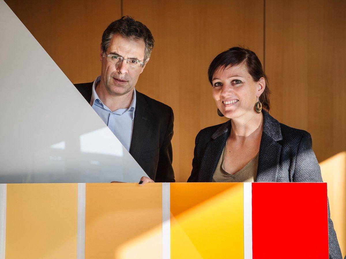 Das weltweit erste weiße Solarmodul präsentieren Professor Christophe Ballif, Vize-Präsident desSchweizer Zentrums für Elektronik und Mikrotechnik (CSEM), und Laure-Emmanuelle Perret-Aebi, Sektionsleiterin beim CSEM. Am unteren Bildrand sind Farbmuster aufgereiht, die mit der CSEM-Technik hergestellt werden können