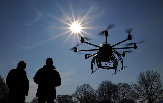 Zwei Männer lassen einen Oktokopter steigen. Der kleine Hubschrauber kann beispielsweise eine Kamera für Luftaufnahmen tragen.