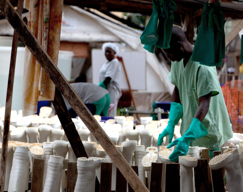 Dutzende Gummistiefel werden in Gueckedou (Guinea) im Ebola-Behandlungszentrum nach dem Desinfizieren getrocknet. Überlebende der Ebola-Erkrankung, nun immun, organisieren in Guinea Hilfe zur Selbsthilfe.
