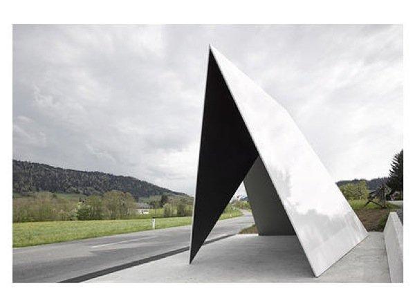 Die flämischen Architekten de Vylder, Vinck, Tailleu, beeindruckt von der Fahrt über die Alpenpässe, haben einen Unterstand gefaltet, in dem sich drei Richtungen treffen. Die Dreiecksform in ihrer minimalistischen Einfachheit strahlt Klarheit und auch Poesie aus.