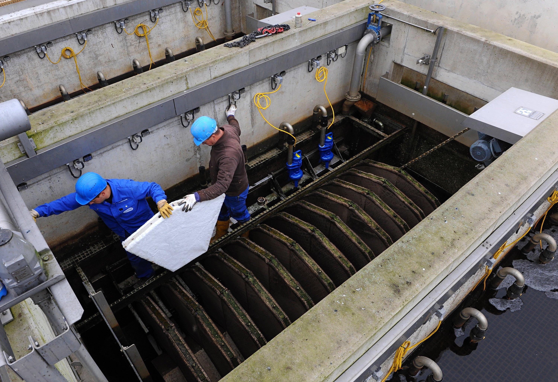 Zwei Mitarbeiter der Kläranlage des Oldenburgisch-Ostfriesischen Wasserverbandes (OOWV) in Oldenburg (Niedersachsen) führen in einem der Klärbecken ein unbenutztes Filterelement zur Absorption von Mikroplastik aus dem Abwasser vor. Insgesamt sind auf dieser Filtertrommel 72 solcher Filterelemente montiert.