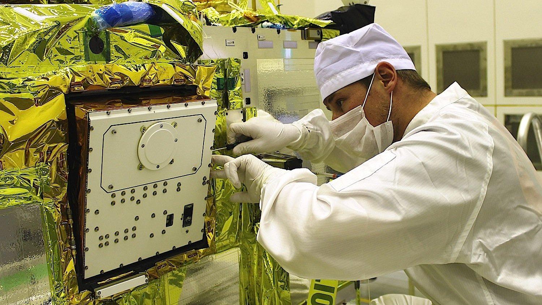 Ein Ingenieur baut den DLR-Asteroidenlander Mascot in dieHayabusa-2-Sonde der japanischen Raumfahrtagentur Jaxa ein.
