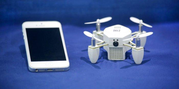 Mini-Drohne Zano neben einem weißen iPhone.