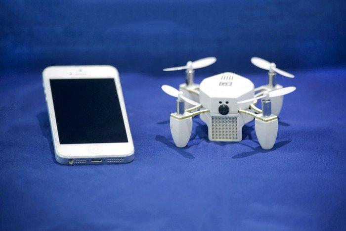 Die Mini-Drohne Zano und das iPhone sind etwa gleich groß.