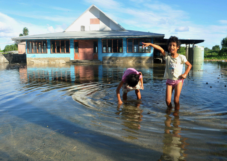 Ihnen bringt der Klimakompromiss von Lima nichts: Kinder spielen auf einem vom Meerwasser überflutetem Platz in Funafuti, der Hauptstadt des nur 26 Quadratkilometer große Inselstaates Tuvaluim Pazifik. Auf den neun Atollen des Inselstaates leben nur 10.700 Einwohner. Der höchste Punkt der Atolle liegt nur vier Meter über dem Meeresspiegel, im Schnitt sind es nur zwei Meter. Daher könnte angesichts des Klimawandes das Staatsgebiet im Meer versinken.