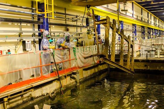 Entfernung radioaktiv verseuchter Metallteile aus dem ältesten Reaktor auf dem Atomgelände in Sellafield: Der Abriss der teilweise noch aus den 1950-er Jahren stammenden Atomkraftwerke stellt hohe technische Ansprüche. Jetzt setzt Sellafield bei den Abrissarbeiten auch 3D-Drucker ein, die nicht mehr verfügbare Ersatzteile herstellen. Einige Anlagen müssen auch beim Abriss zuverlässig funktionieren, was wegen fehlender Ersatzteile immer schwieriger wird.