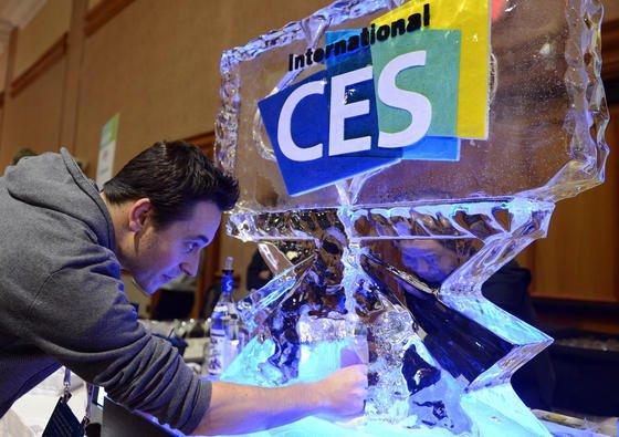 """Ein junger Mann füllt am 5. Januar 2014 in Las Vegas bei der Veranstaltung """"Unveiled"""" im Rahmen der Elektronik-Messe CES (Consumer Electronics Show) sein Glas an einer Eisskulptur. Die Messe läuft offiziell vom 7. bis 10.01.2014."""