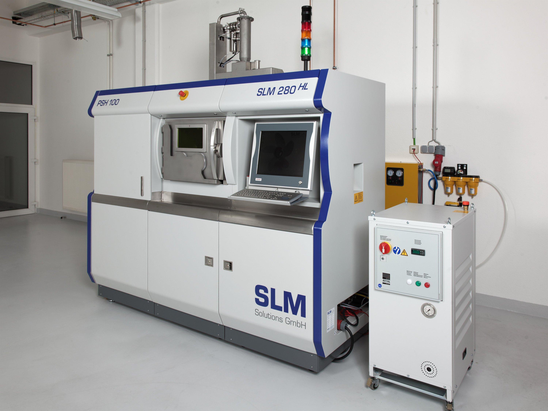 Ein 3D-Drucker des Unternehmens SLMSolutions steht in einer Werkhalle.