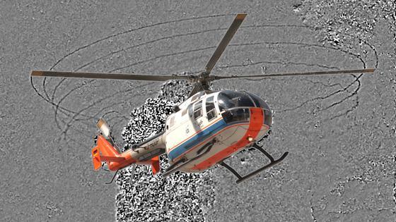 Forscher des DLR ist es gelungen, die Rotorwirbel eines Hubschraubers in Bildern festzuhalten. Die Blattspitzenwirbel sind als dunkle Linien während einer vollen Umdrehung des Hauptrotors sichtbar. Außerdem sind die Abgasstrahlen des Hubschraubers als verrauschte Fläche hinter dem Hubschrauber zu erkennen. Auch das Wirbelsystem des Heckrotors ist zu sehen (schwarze kreisförmige Linien am Heckrotor). Der Hubschrauber führt gerade eine Wippbewegung aus.