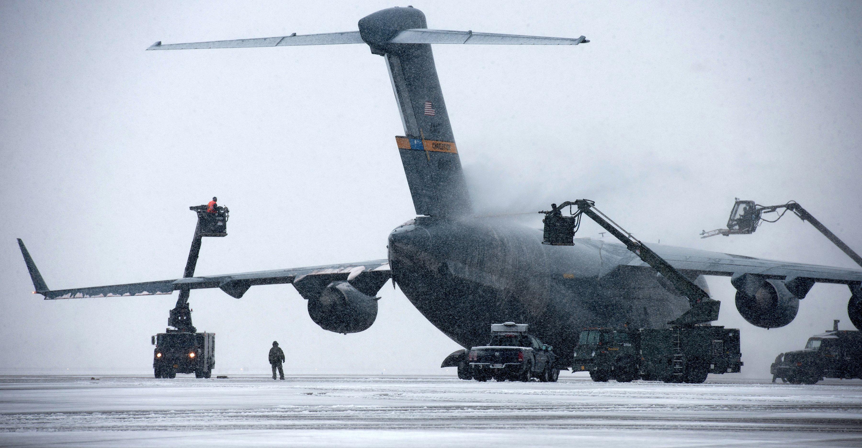 Enteisen einer Boeing C-17 Globemaster III: Die US-Luftwaffe muss bei jedem Wetter fliegen und hat auch während des aktuellen Schneechaos in den USA den Flugbetrieb aufrecht erhalten. Jetzt haben Schweizer Forscher eine Oberflächentechnik entwickelt, die das Vereisen in Zukunft verhindern könnte.