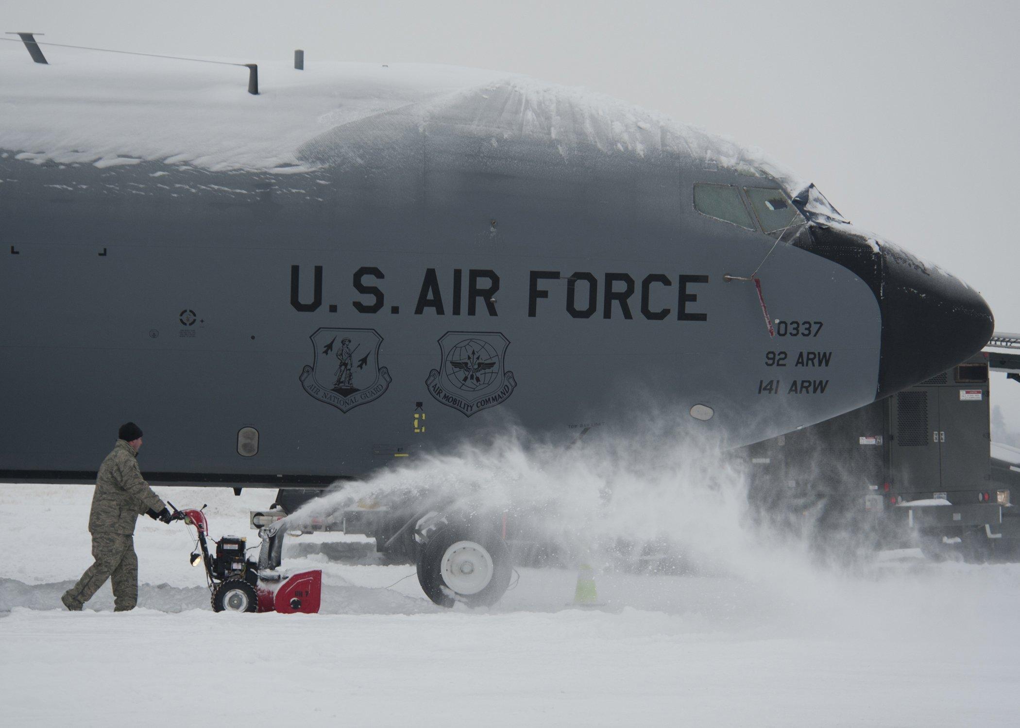 Mit kleinen und noch deutlich größeren Schneepflügen werden die Militärflugzeuge auf amerikanischen Luftwaffenbasen vom Schnee befreit.