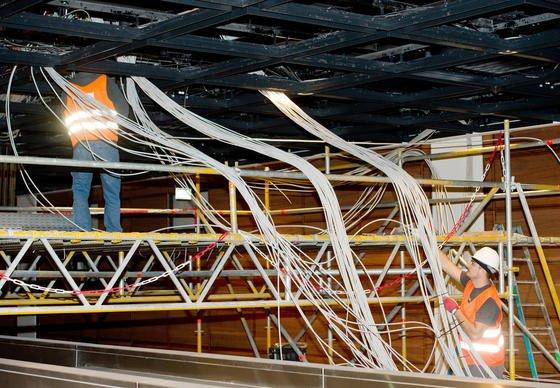 """Arbeiter verlegen Kabel in der Gepäckabfertigung des neuen Flughafens Berlin Brandenburg Willy Brandt (BER) in Schönefeld (Brandenburg). Die Kabelschächte am BER sollen derart """"vollgestopft"""" sein, dass Überhitzung und Schmorbrände bei laufendem Betrieb drohen."""