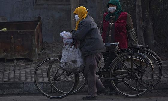 Radfahrer mit Atemmaske in Peking: Ein Teil der hohen Luftverschmutzung in China geht auf die Billigproduktion der Exportindustrie für westliche Länder zurück, so eine Studie der Universität Peking. Inzwischen verwehen die Luftschadstoffe aus China so weit, dass sie bereits die Westküste der USA erreicht haben.